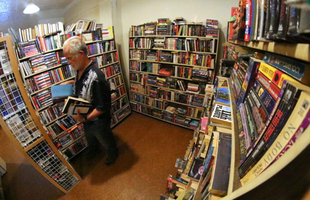 Larry Hoffman browses through the shelves of books at The Rose and Laurel Bookstore, where all the books are free for the taking. For 40 years Rose and Laurel has been a staple storefront in downtown Oneonta, but today they are closing their doors at their location at 273 Main St. Joe Mish, who currently runs the store, is moving down the street into the Shops at Ford and Main where he will continue to sell books. The space is smaller, so all the books he can't take he is giving away. Book lovers can find titles from all genres and titles from the 1800's to current. So, stop in and stock up on next summer's beach reads. The free book event goes until 2pm today. (Ian Austin/AllOTSEGO.com)