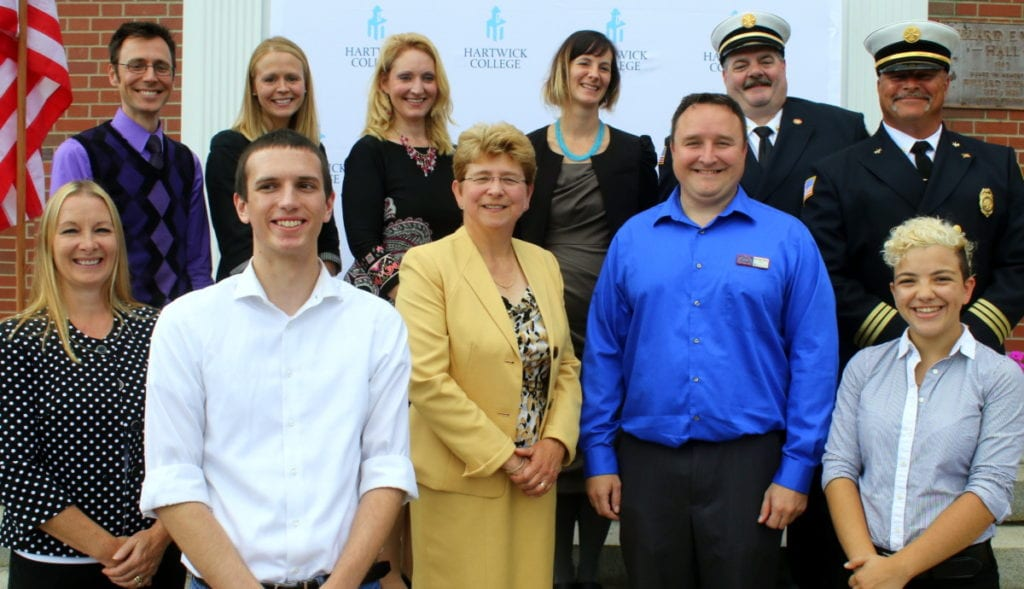 The Otsego County Chamber announced the Hartwick College Craft Food and Beverage Center, Wahl to Wahl auto and interns Demi Manesis and Kevin Zambrzycki as the winners of their annual Small Business Awards this morning in front of the Yager Museum at Hartwick College. Top row, from left: Aaron McCloud, Director of the Hartwick College Food and Beverage Center, ___, Barbara Ann Heegan, President of the Otsego County Chamber of Commerce, ____, Oneonta Fire Chief Pat Pidgeon, Assistant Fire Chief Jim Maloney. Bottom Row: ___, ___, Hartwick College President Margaret Drugovich, small business of the year winner Anthony Wahl, and Demi Manesis. (Ian Austin/AllOTSEGO.com)