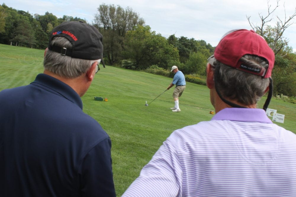 On the green of the Oneonta Country Club, Bob Finnegan and Leon Brown, watch as Tom Anderson takes a swing during the 2nd annual YMCA Golf Outing. The event hosted 19 teams and features raffles and prizes including Calloway Golf Clubs, Expedia tickets, a Webber BBQ grill, TV and a $10,000 hole-in-one prize! All proceeds go to programming at the YMCA. (Ian Austin/AllOTSEGO.com)