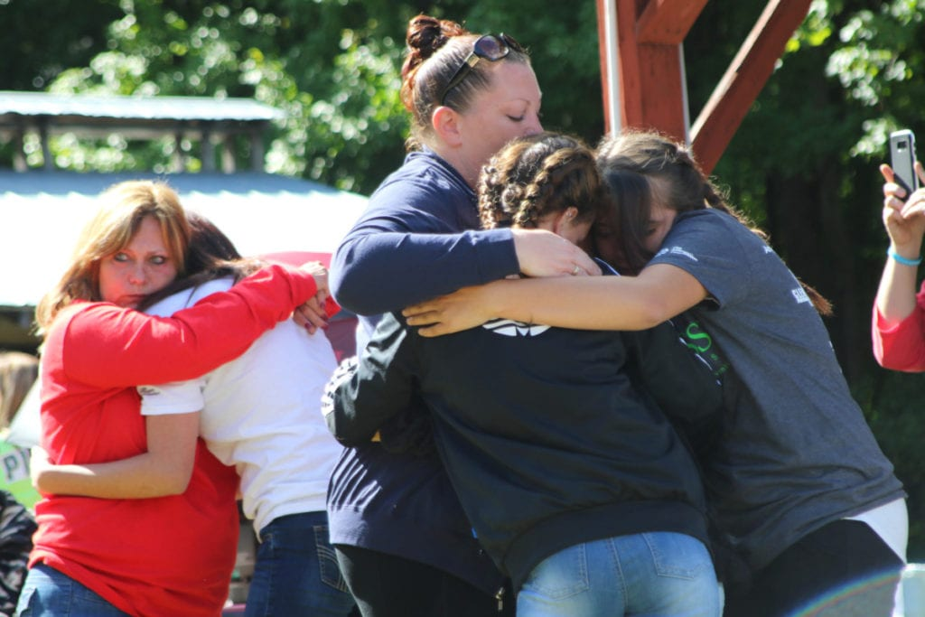 Aubrianna Robinson, Emily Runblad and Deli Lang, front, and event ornagize Donna Lang and Lyla Banhart embrace during a moment of remembrance at the 5th Out Of The Darkness Community Walk at the Moose Lodge in Oneonta on Saturday morning. Friends and families who had lost someone to suicide gathered to show support and to release the stigma surrounding suicide. The names of those lost were read aloud and balloons and pigeons were released before the walk began. The event is part of the American Foundation for Suicide Prevention. More info at afsp.org. (Ian Austin/ALLOTSEGO.com)