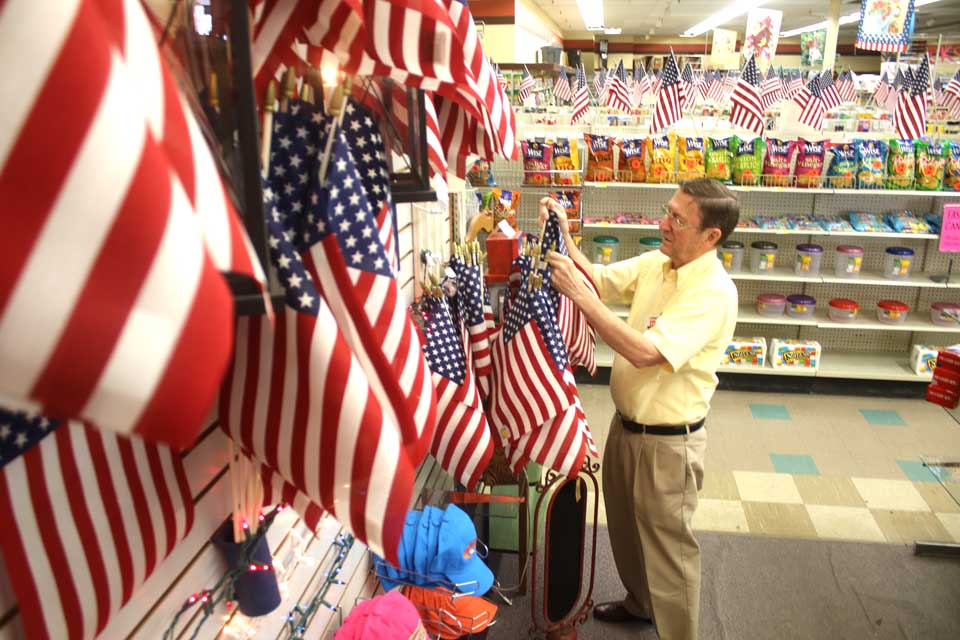 Ron Jax, Cooperstown General Store manager, adjusts the flag display today in preparation for the 15th anniversary of 9/11, coming up next Sunday.  Store employee Deb Graham of Milford set up the display, and lined the display cases in every aisle with American flags.  (Jim Kevlin/AllOTSEGO.COM)