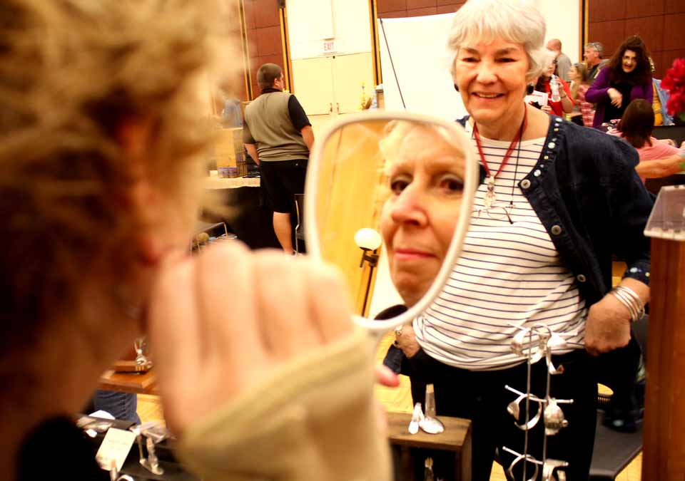 Cindy Struckle of Oneonta tries on a pair of earrings at the arts and crafts fair underway until 4 p.m. at SUNY Oneonta's Hunt Union, part of the college's Family Day activities underway this weekend.  (Jim Kevlin/AllOTSEGO.com)