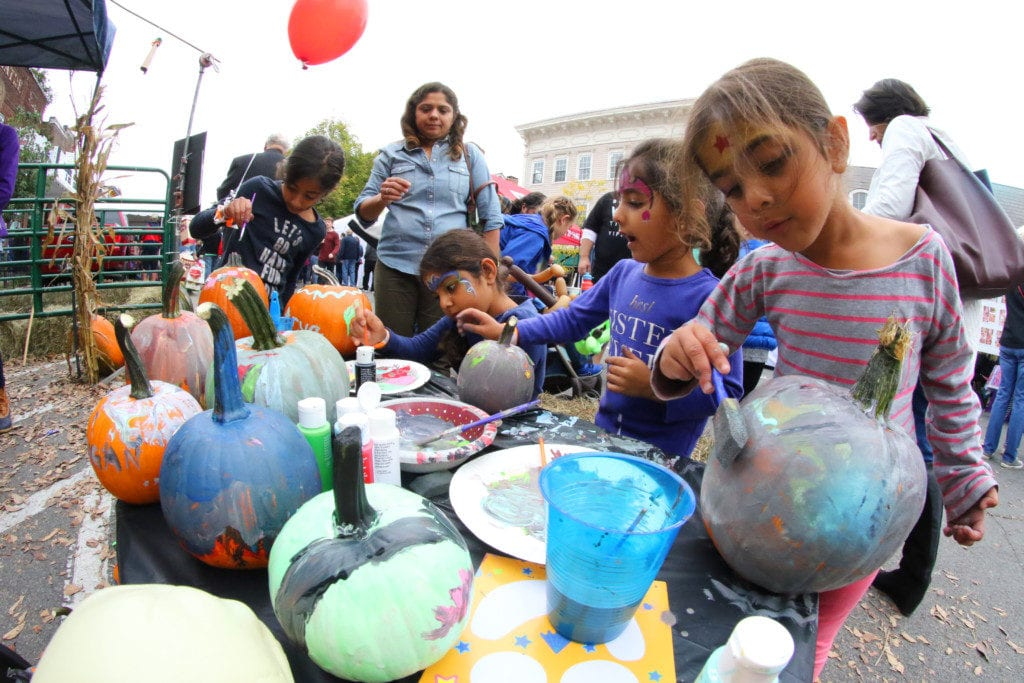 Cooptober Fest was filled with children's activities including bounce houses, face painting, carnival games, painting, train rides and more! Here, Bijal Patel, top, Cooperstown watches her daughter Maya, niece Arya, daughter Mira and niece Avni paint pumpkins at the Cooperstown Lions Club tent. (Ian Austin/AllOTSEGO.com)