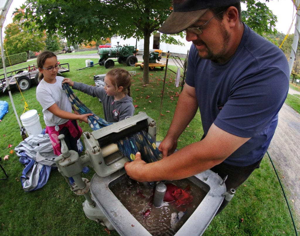 Mike Stevens, Oneonta, enlists the help of his daughters Victoria and Alicia in demonstrating a 1927 Maytag washing machine on display at Tractor Fest at The Farmer's Museum this afternoon. In addition to many antique tractors on display, families can see old fashion hay threshing, try roasted corn, explore the historic village, pet animals and more! The fun continues Sunday 10-5pm. The event funds scholarships for New York college freshmen pursuing careers in agriculture. (Ian Austin/AllOTSEGO.com)
