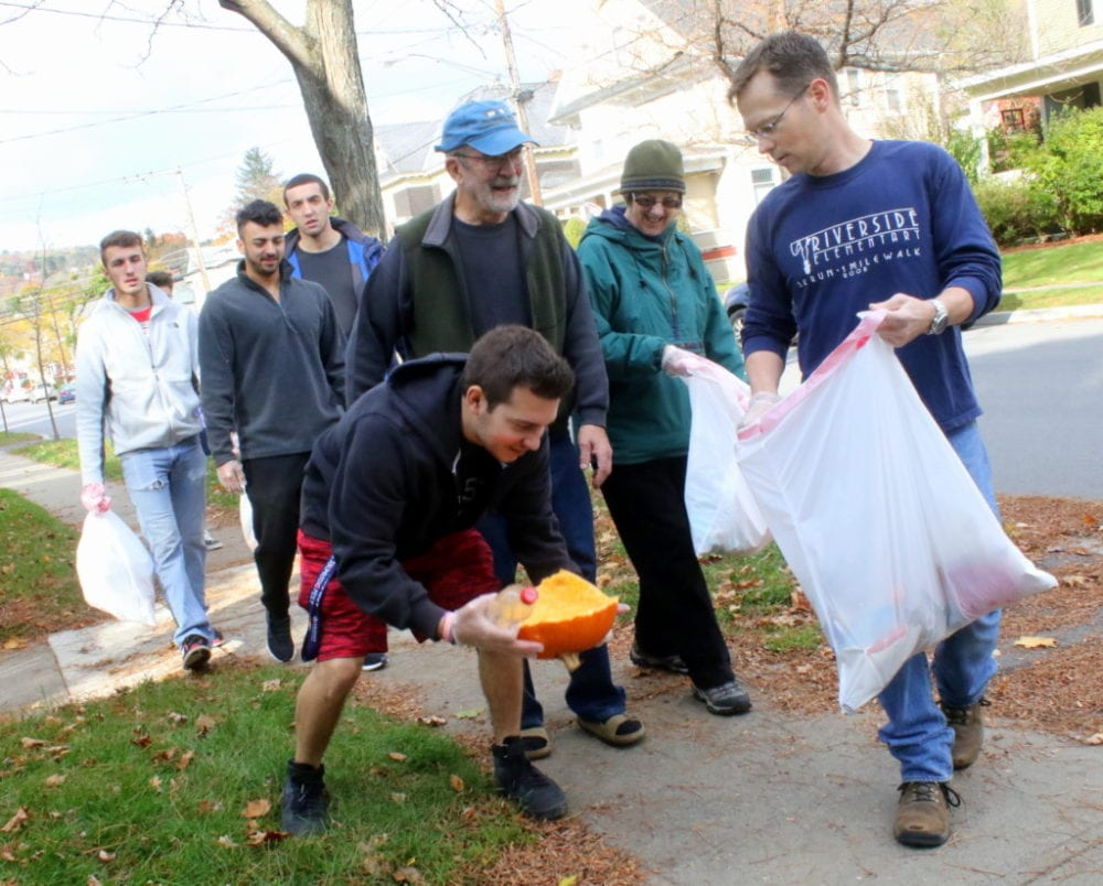 3rd ward councilman Dave Rissberger, right, holds a bag as SUNY volunteer Jacob Perez as he picks up trash along Elm St. Behind them are 3rd ward residents Charlie and Marty Winters, and volunteers from Hartwick's Alpha Omicron Pi and SUNY's Phi Kappa Jon Corado, Dylan Alves and Nick Marcella, who all took part in the 4th annual neighborhood clean up this morning.(Ian Austin/AllOTSEGO.com)