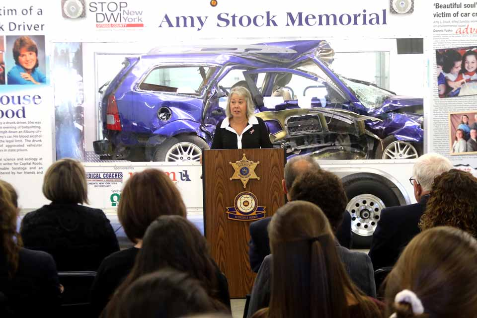 Eileen Anania of Cooperstown reflects on her sister Mary Stock's life, and how her death when her car was struck by a drunk driver's led to a memorial trailer that will be used as a teaching tool in high schools across New York State. Almost 100 friends and well-wishers gathered at 1 p.m. today to honor the Stock family – Mary's parents and six brothers and sisters – who diverted their grief toward a positive outcome. The effort was a collaboration of Mrs. Anania and her family, county Sheriff Richard J. Devlin Jr., ONC BOCES (represented today by Assistant Sperintendent Joe Booan), and Medical Coaches of Oneonta (represented by Len Marsh). (Jim Kevlin/AllOTSEGO.com)