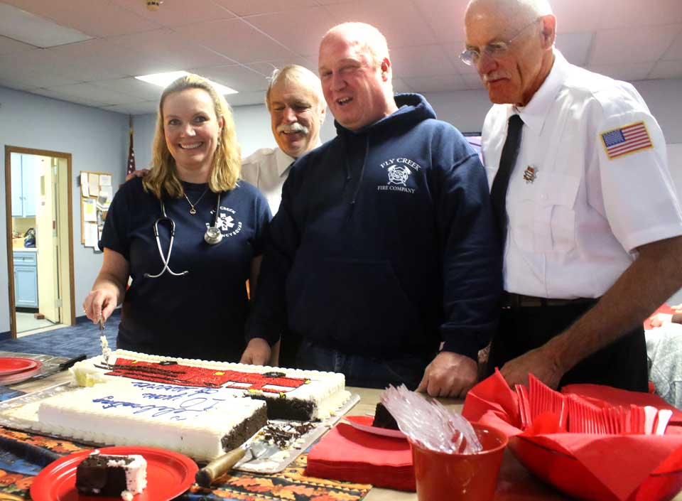 Fly Creek Volunteer Fire Company President Christine Vuolo cuts the cake this morning to make the company's 10th anniversary, assisted by, from left, firefighters John Phillips, Chief Michael Thayer and George Hymas.  The fun continues until 1 p.m.(AllOTSEGO.com photo)