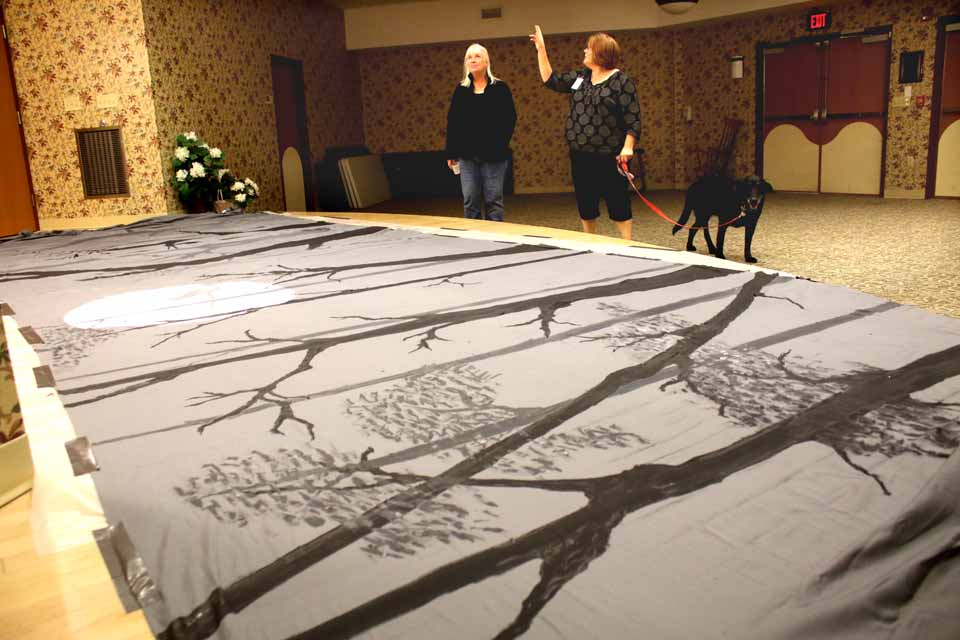 "Focus Otsego art teacher Mary Nolan, left, and activities director Amy Rose examine the spooky backdrop that will be hung in the rehab center's community room Monday, when the Rev. Steve Fournier, pastor, Milford Center Community Bible Church, will do a dramatic reading of Washington Irving's ""Legend of Sleepy Hollow.""  The public is welcome to the 2:30 p.m. gathering.  The backdrop is three king-size sheets glued together and painted with a spooky scene.  The water-based paint will wash off, Rose said, and the backdrop can be repainted for future dramatic presentations.  (Jim Kevlin/AllOTSEGO.com)"