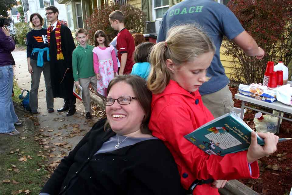 """Elizabeth Dunn provides a comfortable backstop for Charlotte Feury, 9, as she immerses herself in Phineas and Ferb's """"Agent P's Guide to Fighting Evil"""" at the Little Library's inaugural event, which continues until 2:30 p. m. at 42-44 Chestnut St. in Cooperstown. The Little Library is a 70-nation undertaking to help young people share books; the local effort was organized by the Marietta family, dad Andrew, mom Melissa and sisters Caroline and Charlotte. Harry Potter (Mark Conchie of Oneonta), seen in the background, showed up for the event. Among the prizes were county Treasurer Dan Crowell's """"The SEWA Movement & Rural Development,"""" won by Mia Kaltenbach, 9. (Jim Kevlin/AllOTSEGO.com)"""