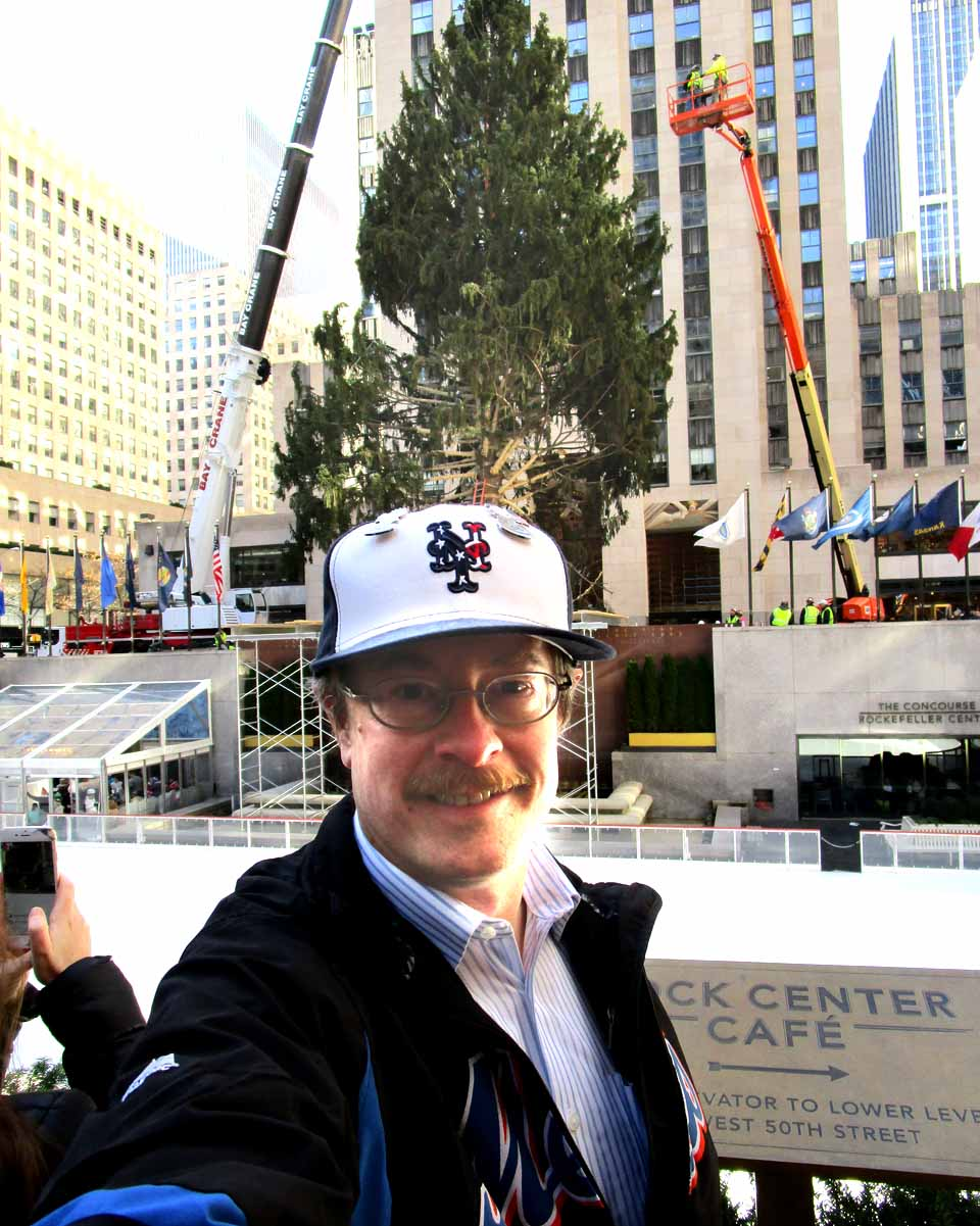 Glenn Linsenbardt of Hartwick, who works for the county Office for the Aging, snaps a photo at Rockefeller Center Saturday, where he witnessed the placement of this year's Christmas tree – it grew on the Eichler family's lot on Country Club Road, Oneonta – next to the rink. The huge will decorated and lit on Nov. 30. Lisen