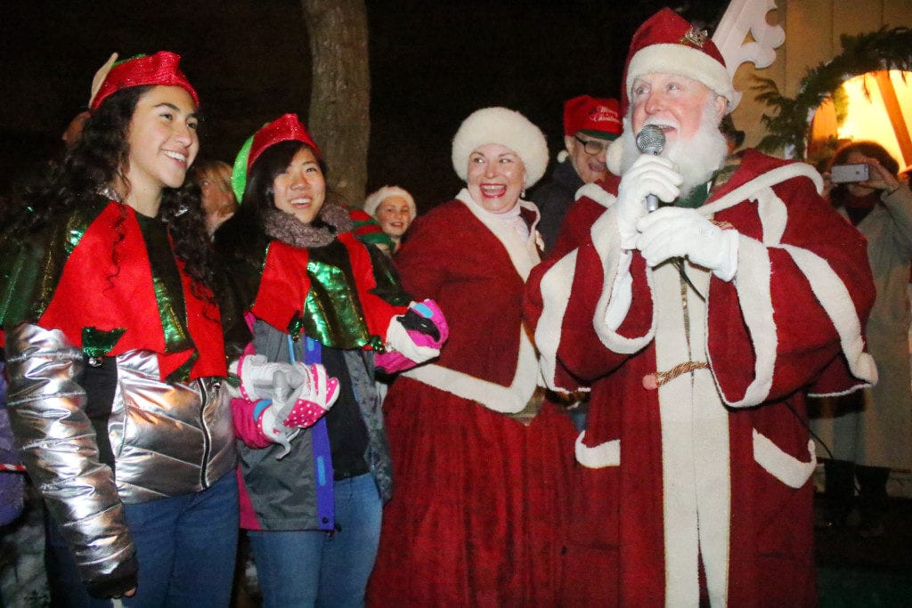 """Children and adults alike lined the streets around Pioneer Park this evening to welcome the Mr. and Mrs. Claus to their seasonal home in Cooperstown. Student volunteers like Jessica Becerra and Chihiro Kapafuchi, Cooperstown, as well as Frosty, Rudolf and elves were seen throughout the crowd posing for pictures and handing out candy canes ans spreading holiday cheer. Before receiving his first visitors of the season, Santa addressed the crowd; """"Do you know why we chose our second home to be here?"""" he asked, """"Because you have the best Christmas spirit!"""" (Ian Austin/AllOTSEGO.com)"""