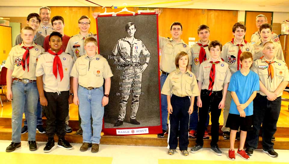 """Members of Cooperstown Boy Scout Troop 1254 poses a few minutes ago with a newly completed quilt square commemoration Hank Nicols, a troop member who contracted the disease in the 1980s while receiving blood transfusions to treat his hemophilia.  The square – 3 by 6 feet, the size of a coffin – is the second one completed by Hank's mother Joan.  His father, also Hank, is a troop leader.  The troop then watched """"Eagle Scout: The Story of Henry Nicols,"""" an HBO film recounting how the young man announced his diagnosis 25 years aog, then campaigned for AIDS awareness before succumbing to the disease in 2007.  (Jim Kevlin/AllOTSEGO.com)"""
