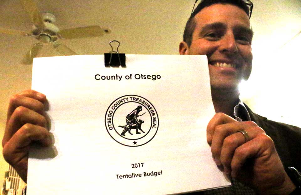 With a smile, County Treasurer Dan Crowell holds up the preliminary 2017 county budget that he submitted Tuesday, a day ahead of the requirement, to Clerk of the Board Carol McGovern. (Jim Kevlin/AllOTSEGO.com)