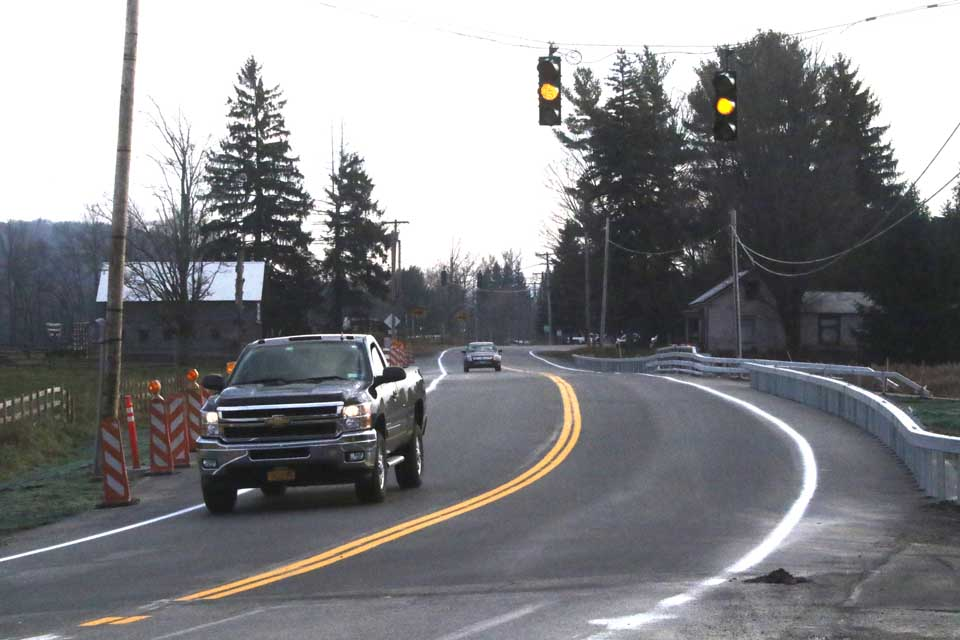 Traffic was flowing smoothly again yesterday over the Route 28 bridge just north of Schuyler Lake, which has been limited to single-lane traffic as the state DOT replaced the span over Herkimer Creek this summer.  Both lanes are open and the light is blinking orange as a Region 2 crew finishes the final touches.  (Jim Kevlin/AllOTSEGO.com)