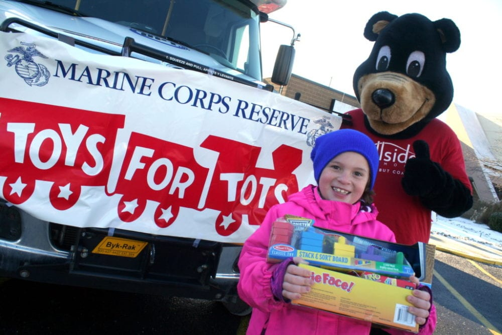 "It is a chilly morning, but that didn't keep Desiree Wheeler and the Hillside Commons Bear from standing outside the annual Fill The Bus event to benefit Toys For Tots Drive at the Southside Mall this morning. The bus, provided by OPT in conjuction with Hillside Commons, will be at the mall from 9am-11am on Saturday. Toys can still be dropped off at many locations around town before they are collected on December 14th. ""I didn't get a lot of toys this year."" said organizer Sharron Wheeler, ""I am still about 700 toys short. I hope our County can step up to help the kids this Holiday season."" If you would like more information, or, to drop off toy donations, call 607.432.7052. (Ian Austin/AllOTSEGO.com)"